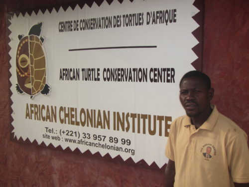Marcel (Rhodin Center employee) next to the entrance sign of the Rhodin Center